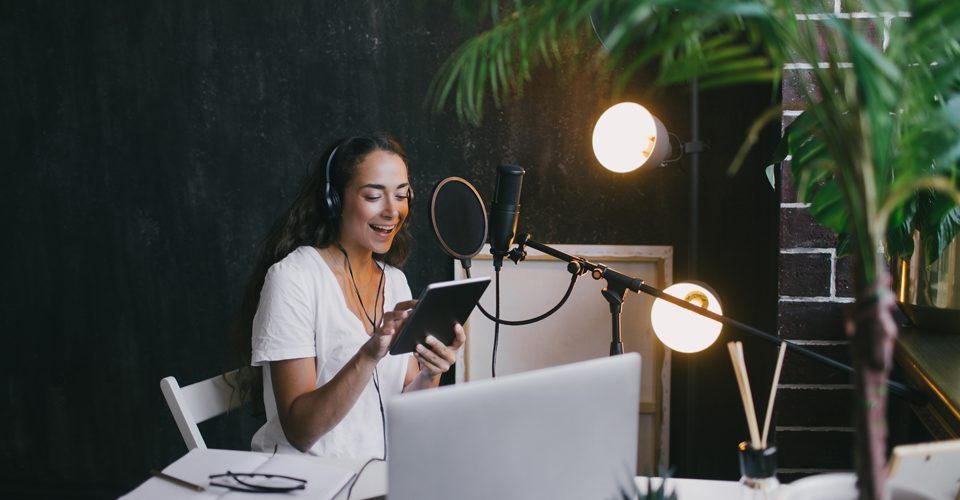 Woman sitting at microphone recording a podcast